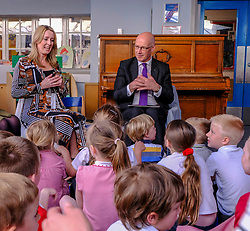 Pictured: Teacher Lisa Black and John Swinney lead the students in reading and singing<br />