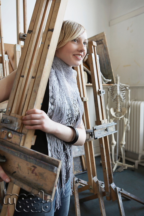 Art student carrying easel into studio