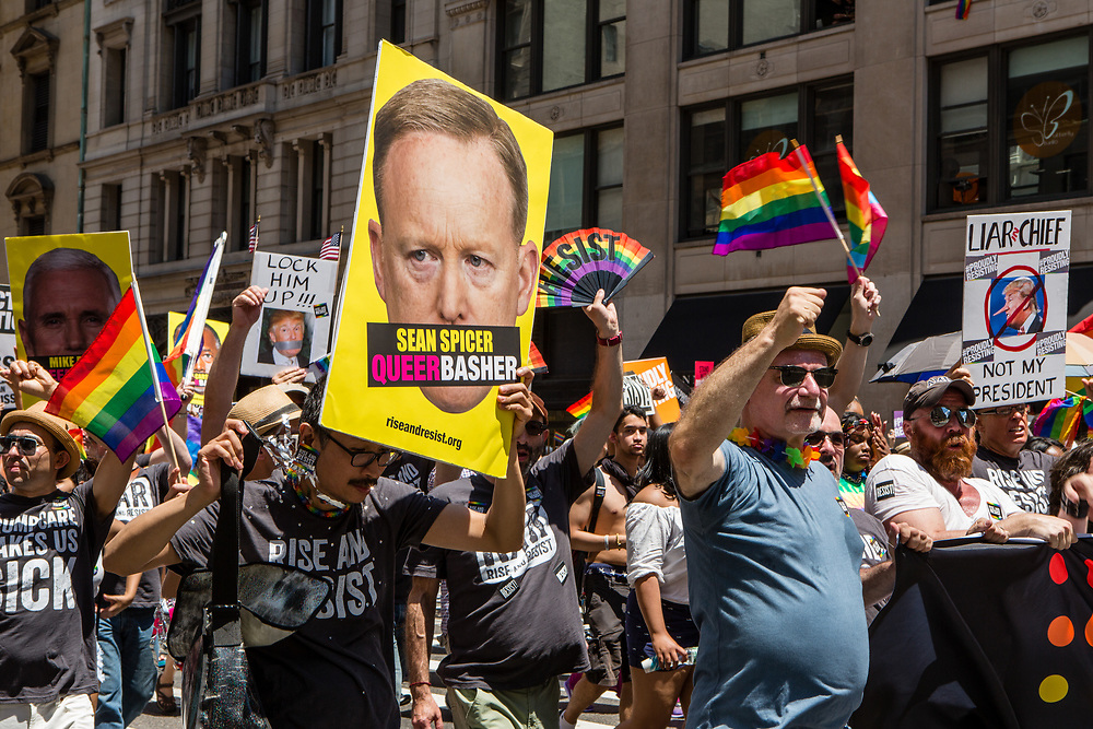 "New York, NY - 25 June 2017. New York City Heritage of Pride March filled Fifth Avenue for hours with groups from the LGBT community and it's supporters. A large contingent of marchers from Rise and Resist, many of whom were carrying signs, the largest of which here has a large photo of White House Press Secretary Sean Spicer, with the banner ""Sean Spicer / Queer Basher."" superimposed over his mouth."