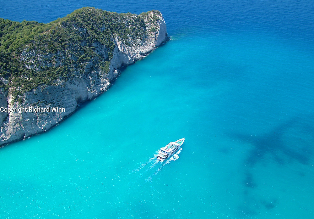Tourist boat leaving the shipwreck at Smugglers Cove, in Zakynthos, Greece. The wideangle view, also shows the edge of the cove itself and some plane-shaped reefs. Zakynthos is one of the Ionian islands and is also known as Zante, a name stemming from the time when it was a Venetian colony. It suffered from a major earthquake in 1954, when all but one building was destroyed. It is also the home of one of the major Loggerhead Turtle breeding grounds. To be used under licence only, subject to agreed terms of the Royalty Free licence. Purchase of a licence does not indicate a transference of the rights and all copyrights remain with the photographer.