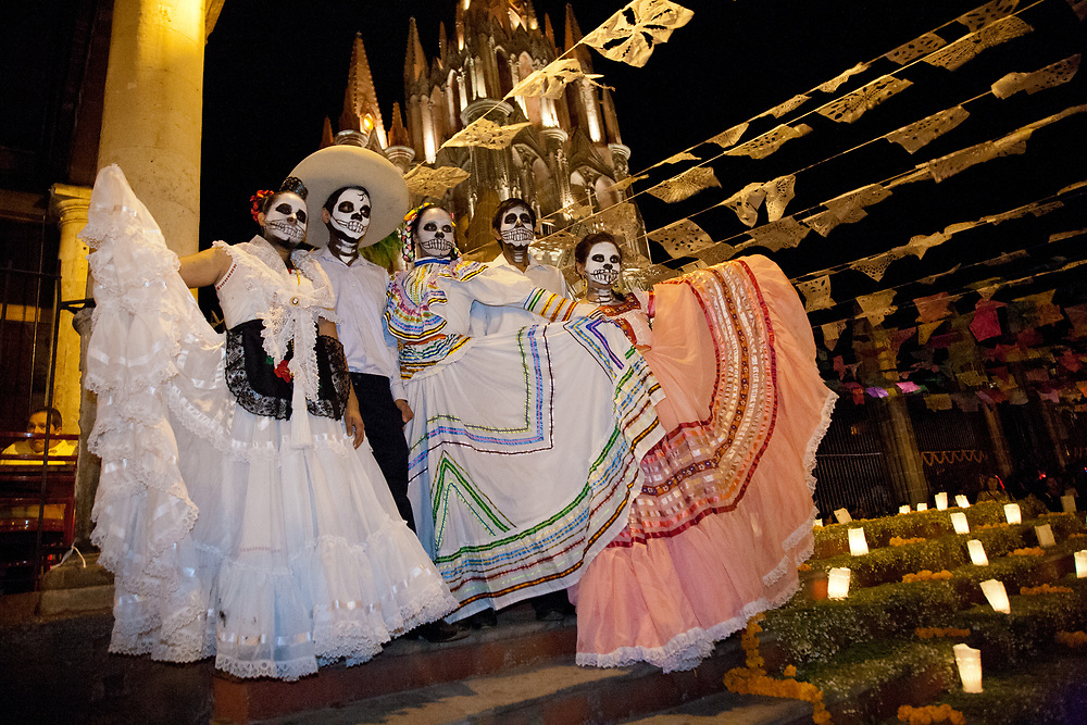 "North America, Mexico, San Miguel de Allende, teenagers in traditional costumes for Day of the Dead parade stand in front of La Parroquia de San Miguel Church, with its negothic facade floodlit at night, and streamers of tissue paper flags, known as ""Papel Picado."""