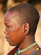 Africa, Tanzania, members of the Datoga tribe Woman in traditional dress, beads and earrings. Beauty scarring can be seen around the eyes, October 2008