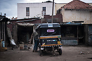 A man reaching into a rickshaw while he works on maintenance in front of his house. Bangalore, India