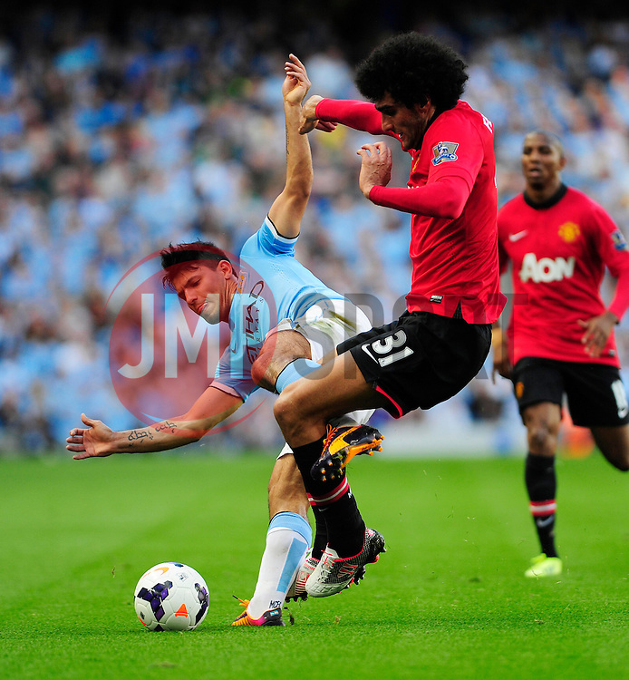 Manchester City's Sergio Aguero and Manchester United's Marouane Fellaini jostles for the ball - Photo mandatory by-line: Dougie Allward/JMP - Tel: Mobile: 07966 386802 22/09/2013 - SPORT - FOOTBALL - City of Manchester Stadium - Manchester - Manchester City V Manchester United - Barclays Premier League
