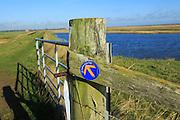 Suffolk Coast path sign along flood defence wall, near Shingle Street, Suffolk, England, UK