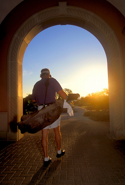 Stock photo of a man heading home at sunset after a day on the links.