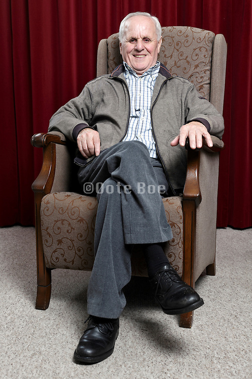 portrait of a happy smiling 89 year old man sitting comfortable in an armchair