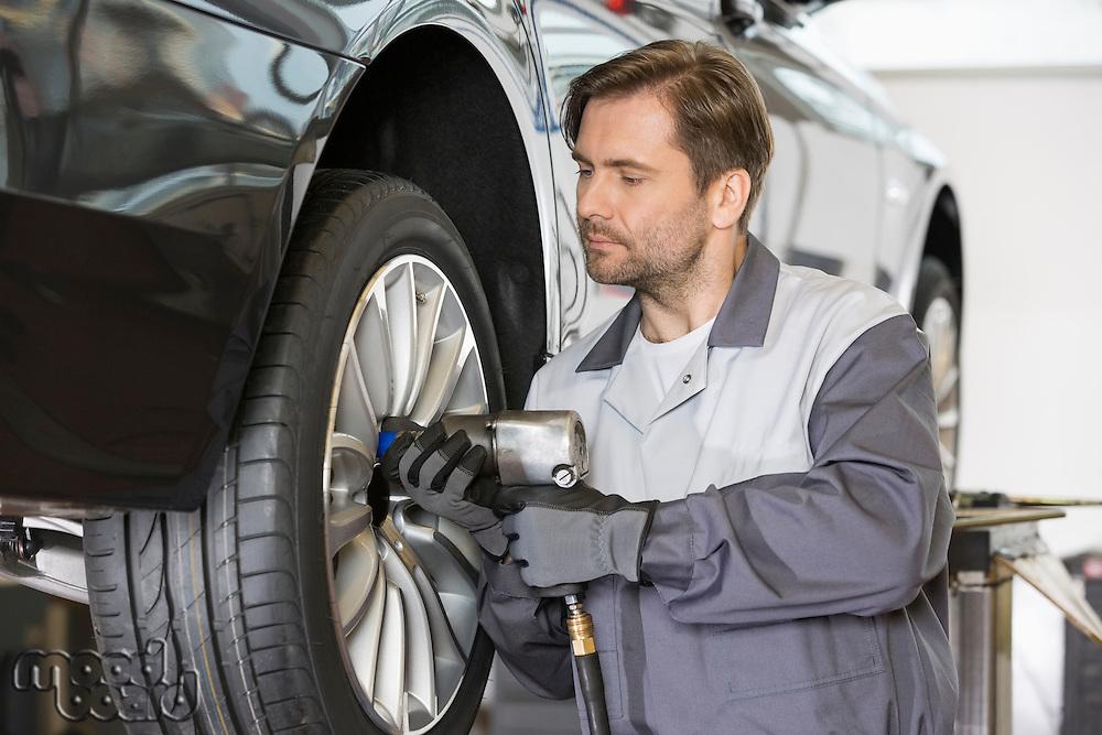 Male mechanic repairing car's wheel in workshop