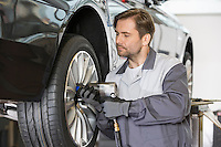 Male mechanic repairing car's wheel in workshop