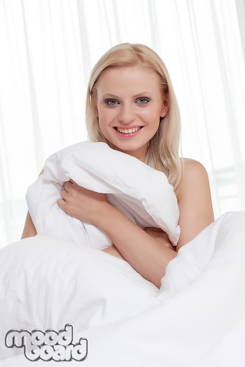 Portrait of beautiful young woman covering herself with bedsheet in bed