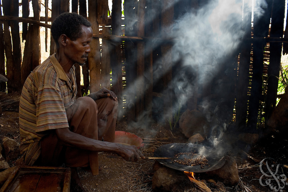 An Ethiopian man roasts coffee beans over an open fire during a local coffee ceremony February 23, 2007 in Fero, Ethiopia in the southern Sidamo coffee region. Ethiopia is the birthplace of arabica coffee, and the coffee ceremony, which is the process of roasting green coffee beans, grinding them, burning incense and joining together to share a cup is a daily tradition for many Ethiopians.