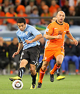 CAPE TOWN, SOUTH AFRICA- Tuesday 6 July 2010, Walter Gargano kicks the ball away from Demy De Zeeuw during the semi final match between Uruguay and the Netherlands (Holland) held at the Cape Town Stadium in Green Point during the 2010 FIFA World Cup..Photo by Roger Sedres/Image SA