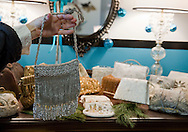 Jennifer Thompson holds a purse for sale at Lush Couture, 329 10th Ave. SE Suite 123 in Cedar Rapids on Friday, December 14, 2012.