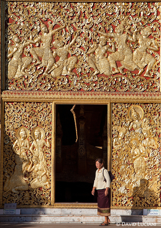 Woman standing near the golden entrance of the funeral chapel of Wat Xieng Thong.
