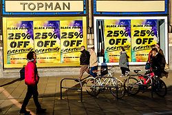 People walking past 'Black Friday' posters in a shop window in Princes Street, Edinburgh on 29th November 2019