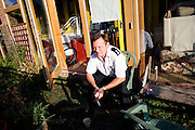 Danny Burrage, a local fireman, having a coffee and a cigarette in front of his house in BedZED on Thursday, Sep. 6, 2007, in London, UK. BedZED or the Beddington Zero Energy Development, is an environmentally-friendly housing development near Wallington, England in the London Borough of Sutton. It was designed by the architect Bill Dunster who was looking for a more sustainable way of building housing in urban areas in partnership between the BioRegional Development Group and the Peabody Trust. There are 82 houses, 17 apartments and 1,405 square meters of work space were built between 2000. The project was shortlisted for the Stirling Prize in 2003. The project is designed to use only energy from renewable source generated on site. In addition to 777 square meters of solar panels, tree waste is used for heating and electricity. The houses face south to take advantage of solar gain, are triple glazed and have high thermal insulation while most rain water is collected and reused. Appliances are chosen to be water efficient and use recycled water wherever possible. Low impact building materials were selected from renewable or recycled sources and were all originating within a 35 mile radius of the site to minimize the energy required for transportation. Also, refuse collection facilities are designed to support recycling and the site encourage eco-friendly transport: electric and LPG cars have priority over petrol/diesel cars, and electricity is provided by parking spaces appositely built for charging electric cars.