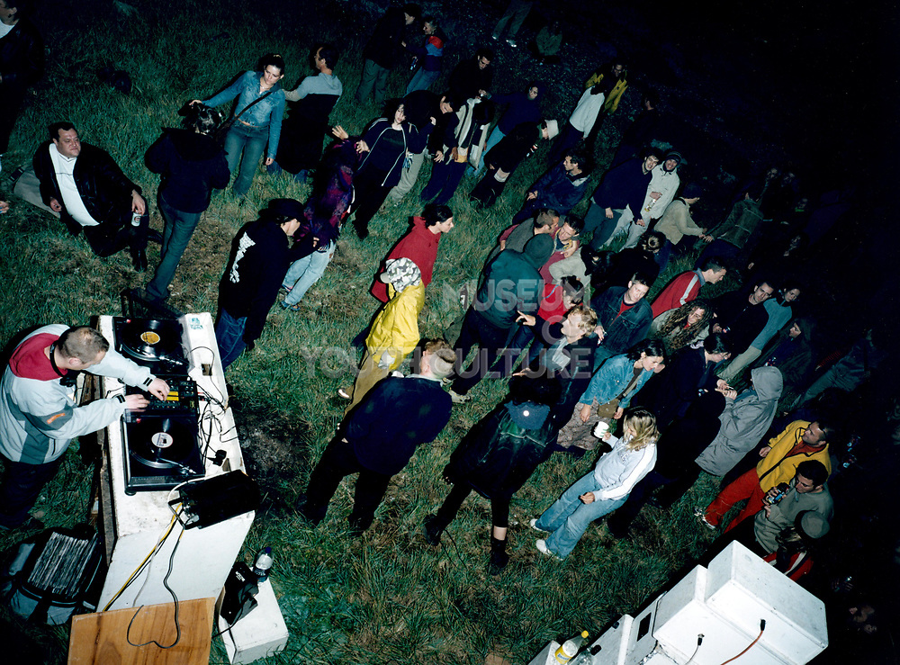 Group of young people having a party outside with a Dj.