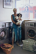 Ebina and Mickey in a launderette, Ebina manages a very expensive and sexy lingerie shop in Soho. She believes that a girl should never be seen leaving the house without her lipstick. Mickey the dog lives on Evian water and Marks and Spencer's 100% prime beef. Westbourne Grove, London, 2004