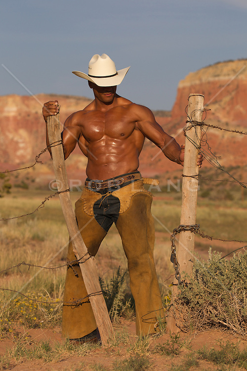 sexy and rugged African American Cowboy outdoors working on a fence without a shirt