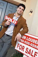 Contented estate agent outside newly sold house
