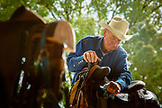 Cowboy shines his saddle.<br />