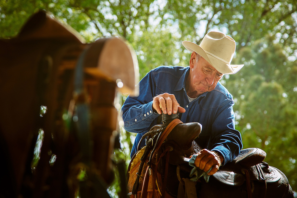 Cowboy shines his saddle.<br /> Country lifestyle.<br /> Photographed by editorial lifestyle photographer Nathan Lindstrom