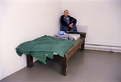 Teenage young offender sitting on bed in corner of police cell following arrest and detention,