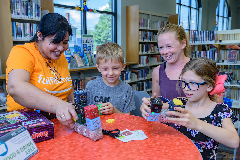 Amazon associate Yany Diaz, left, shows Cubelets to Caiden Downs, 6, his mother Stacie Downs and sister Madison Downs, 8, of Mt. Washington, Ky. Leaders from Amazon present a donation of $10,000 in new technology to support Bullitt County Library's STEM and STEAM programs for students in the Bullitt County School District Tuesday, July 10, 2018 at the Ridgway Memorial Library in Shepherdsville, Ky. The donation will enhance the library's current Digital Tech and Makerspace Lab programs and ignite more students to take advantage of STEM education outside of the classrooms and included Oculus Go headsets, a Cubelets classroom, and several sets of LEGOs that will increase the lab's ability to help students learn and explore STEM. (Photo by Brian Bohannon)