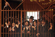 A group of ultra-Orthodox Jewish men look through a fence as the body of Grand Rabbi Moses Teitelbaum, worldwide spiritual leader of tens of thousands of members of the ultra-Orthodox Jewish sect, Satmar Hassidim, is carried into the Yetev Lev D'Satmar synagogue in Brooklyn, New York after he died in New York City at the age of 91 Monday 24 April 2006.