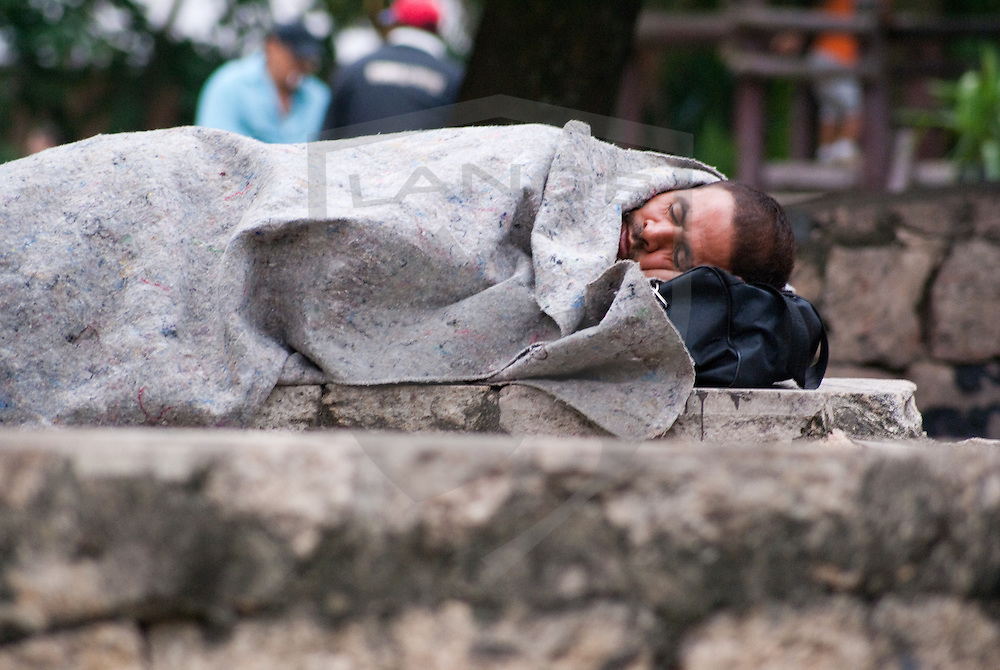 a homeless carioca head sticks out from underneath a blanket in centro, rio de janeiro, brazil.  the disparity in wealth distribution within the city of rio de janeiro is jarring as the government continues to implement legislation to curb the polarized socioeconomic climate.