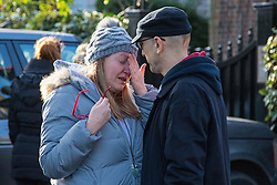 Highgate, London, December 26th 2016. Fans gather outside the London home of pop icon George Michael who died on Christmas day. PICTURED: A man comforts a grief-stricken woman.