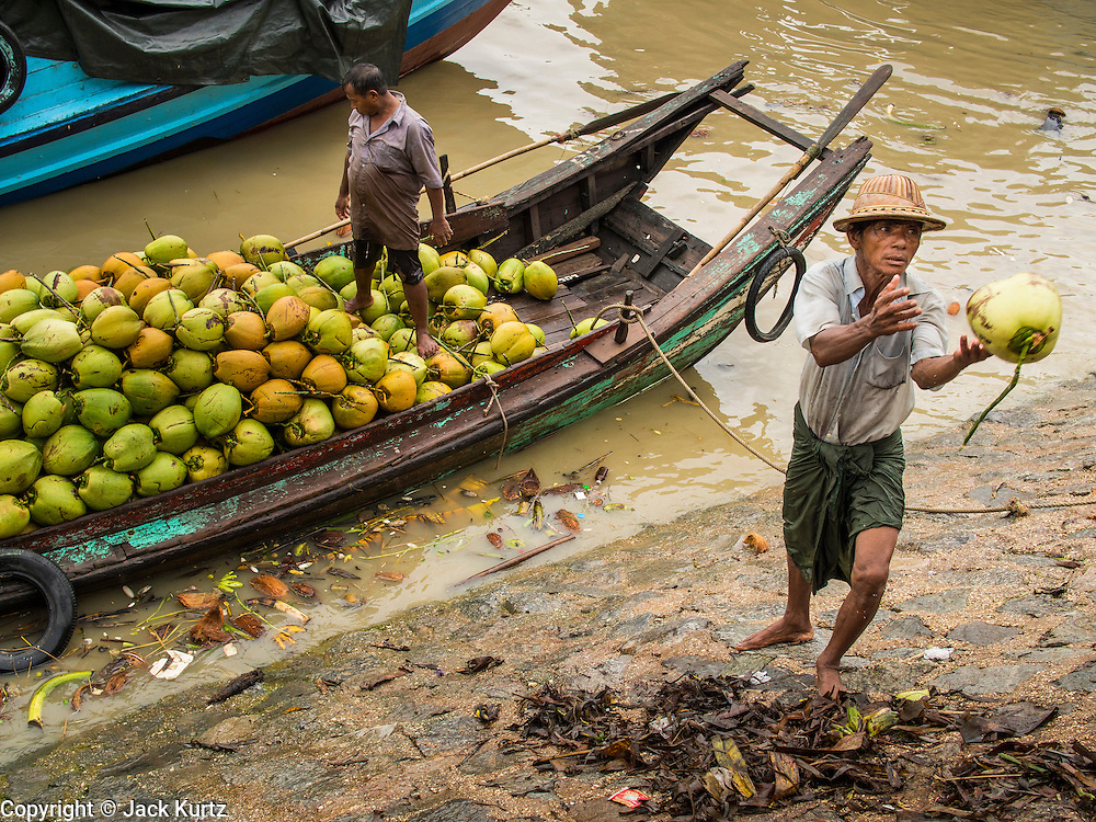 "10 JUNE 2014 - YANGON, MYANMAR:   Porters unload coconuts from a riverboat on the banana jetty. They unload the coconuts by throwing each coconut from the boat to a waiting truck on the shore. The ""banana jetty"" is on the Yangon River north of central Yangon on Strand Road. Bananas, coconuts and other fruit are brought in here from upcountry, sold and reshipped to other parts of Myanmar (Burma). All of the labor here is done by hand. Porters carry the produce to the jetty and porters load the boats before they steam upriver.   PHOTO BY JACK KURTZ"