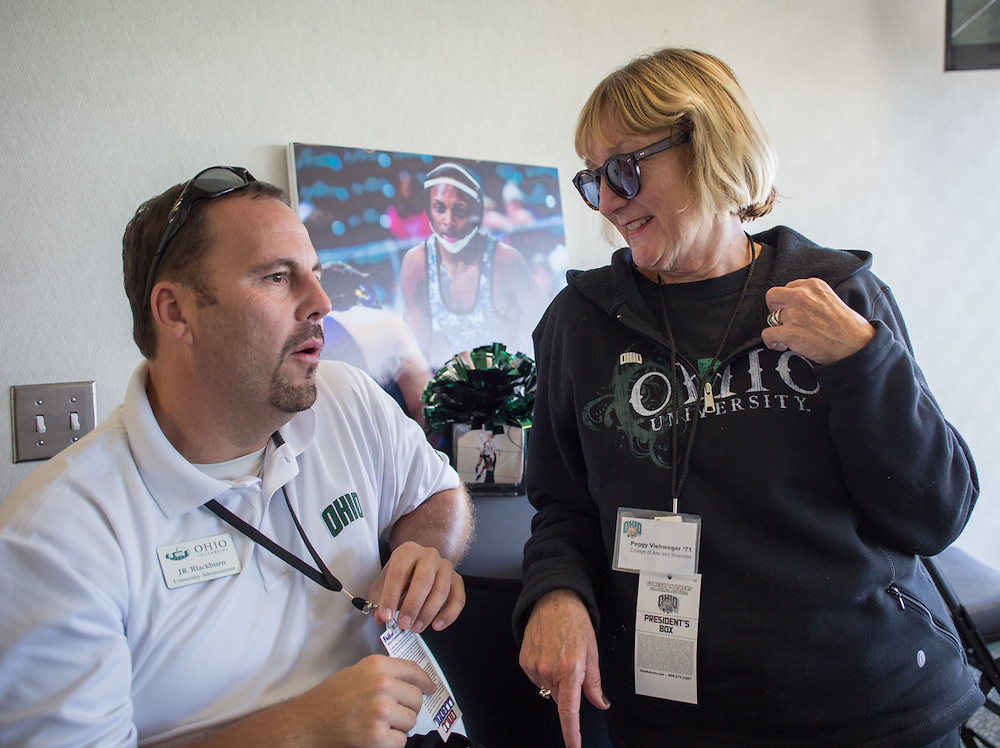 JR Blackburn, Assistant Vice President for Development and Associate Campaign Manager, left, talks with Peggy Viehweger, an Ohio University alumna and a national trustee on the Ohio University Board of Trustees, right, during the Ohio University Homecoming football game at Peden Stadium on October 10, 2015. Photo by Emily Matthews