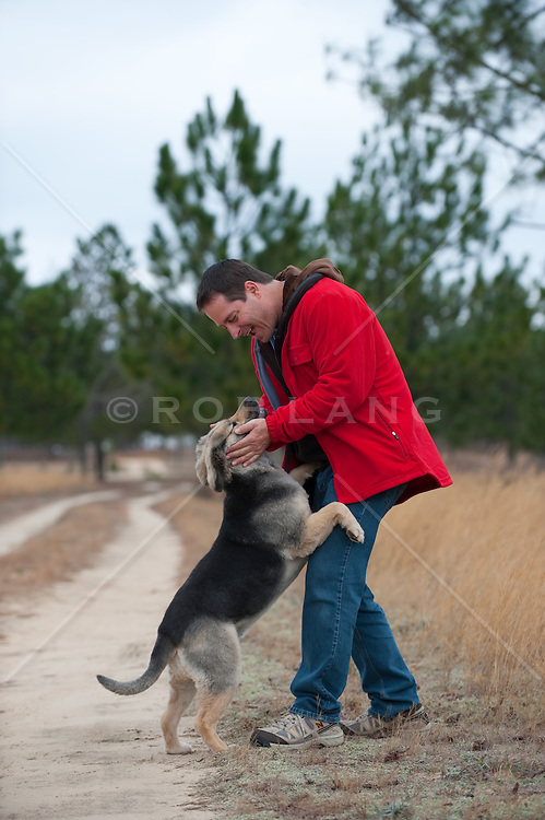 man and a Shepard Mix puppy enjoying time together on a dirt road