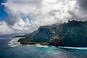 Cloudy Na Pali Coast sea cliffs rise above Ke'e Beach seen via helicopter over the island of Kauai, Hawaii, USA.