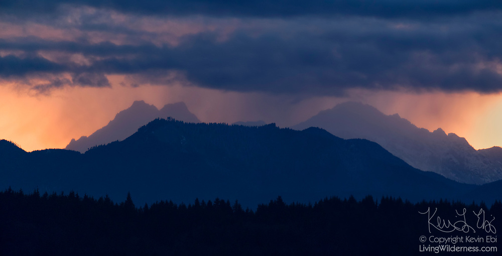 A heavy rainstorm passes over the Olympic Mountains — including the Brothers, which is visible at left — at sunset, in this view from Hood Canal near Hansville, Washington.