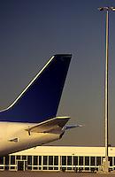 Passenger jet tailplane against airport terminal