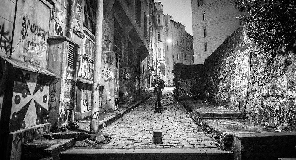 A adult male walks alone down cobblestone alleyway in between buildings in Istanbul, Turkey