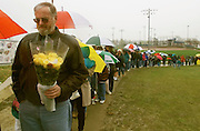 DEN106D:CRIME-SHOOTING:LITTLETON,COLORADO,01MAY99 - Mike Hart of nearby Englewood, Colorado clutches a bouquet of yellow roses May 1 waiting in a pouring rain with hundreds of others to pay respects at a memorial to those killed in the Columbine High School shootings.  Hart had waited an hour to lay the flowers at crosses of the dead. rtw/Photo by Rick Wilking