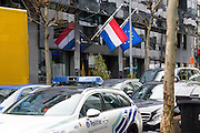 Brussels 23 March 2016 The embassy of the Netherlands with the dutch and European flag hanging half mast. Belgian police car in foreground