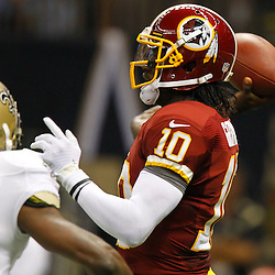 September 9, 2012; New Orleans, LA, USA; Washington Redskins quarterback Robert Griffin III (10) throws a touchdown as New Orleans Saints safety Malcolm Jenkins (27) pressures during the first quarter of a game at the Mercedes-Benz Superdome. Mandatory Credit: Derick E. Hingle-US PRESSWIRE