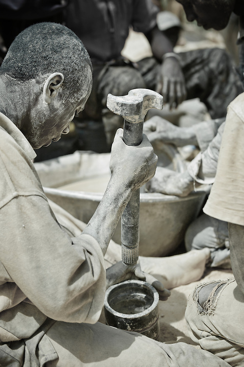 Stock photograph of an African gold miner in Burkina Faso crushing a sample of ore that will then be panned and inspected for gold nuggets.