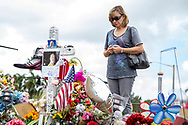 A woman holding a rosary prays outside Marjory Stoneman Douglas High School were a memorial was placed honoring the lives of those lost after a gunman opened fire inside the school during regular class time killing 17 students and staff in total on Wednesday, February 14, 2018<br /> <br /> by Samuel Navarro