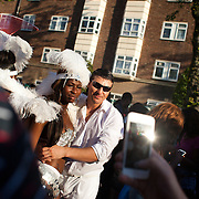 A spectator has his photograph taken with a young dancer. The Notting Hill Carnival has been running since 1966 and is every year attended by up to a million people. The carnival is a mix of amazing dance parades and street parties with a distinct Caribbean feel.
