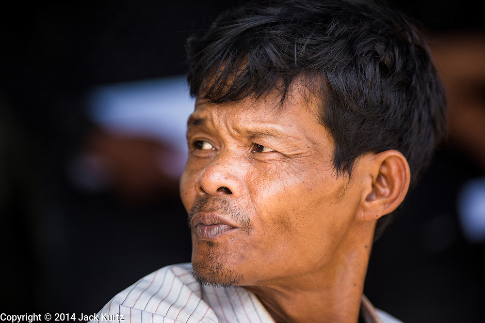 09 JULY 2014 - ARANYAPRATHET, SA KAEO, THAILAND: A Cambodian migrant worker waits to go into the Thai Immigration One Stop Service Center in Aranyaprathet on the Thai-Cambodian border. More than 200,000 Cambodian migrant workers, most undocumented, fled Thailand in early June fearing a crackdown by Thai authorities after a coup unseated the elected government. Employers have been unable to fill the vacancies created by the Cambodian exodus and the Thai government has allowed them to return. The Cambodian workers have to have a job and their employers have to vouch for them. The Thai government is issuing temporary ID cards to allow them to travel openly to their jobs. About 800 Cambodian workers came back to Thailand through the Aranyaprathet border crossing Wednesday. The Thai government has opening similar service centers at three other crossing points on the Thai-Cambodian border.    PHOTO BY JACK KURTZ