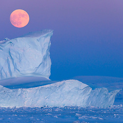 The rising moon glows orange over northern Greenland.