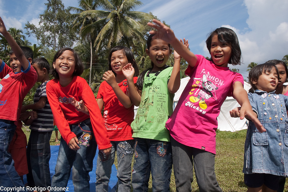Girls laugh during a game outside Save the Children's tented space in the village of Mangur.