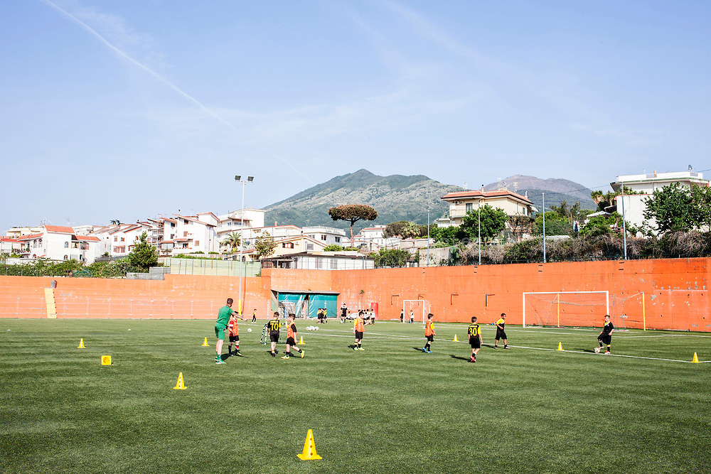 22 May 2017, San Sebastiano al Vesuvio, Naples Italy - Guys plays football inside the field of sport center of San Sebastiano al Vesuvio. Behind the scene the volcano Vesuvius.