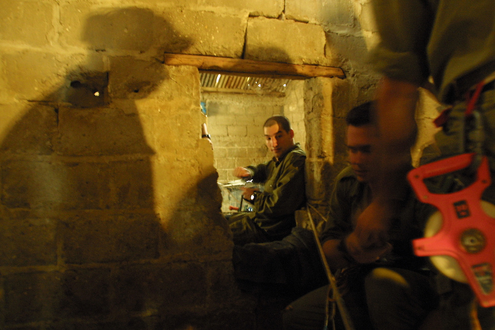 "Israeli soldiers with a special forces unit tasked with finding and destroying weapons smuggling tunnels in Gaza break through a wall to pass from house to house in order to avoid walking exposed in the streets of Khan Younis refugee camp, near the ""Philadephi Road,"" a stretch of road that runs along Gaza's border with Egypt, on July 4, 2004."
