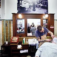 Nederland,  Amsterdam, 7 mei 2014.<br /> Barbier keert terug op Beursplein 5.<br /> Na een jarenlange afwezigheid keert de alom bekende barbier terug op de Amsterdamse beurs. In 1934 werd de Beurs Salon (later: De Barber Shop) geopend in het beursgebouw op Beursplein 5. Voordat zij de handelsvloer betraden werden beurshandelaren op klassieke wijze geknipt en geschoren. De barbier verdween echter in 1996 uit het beurspand.<br /> De beursbarbier keert terug nu Beursplein 5 weer druk bevolkt is door handelaren. De barbiers van Cut Throat Barber & Coffee uit de Warmoesstraat doen een oude traditie herleven en zullen iedere woensdag beurshandelaren knippen en scheren met hun 'Cut Throat Shaves', in een van de authentieke kappersstoelen te Beursplein 5. Het is het resultaat van een bijzondere samenwerking tussen buren in een van de oudste delen van Amsterdam.<br /> Beursbekendheid Peter Paul de Vries zal als eerste plaatsnemen in de kappersstoel om 'geknipt en geschoren' te worden. <br /> <br /> Foto:Jean-Pierre Jans